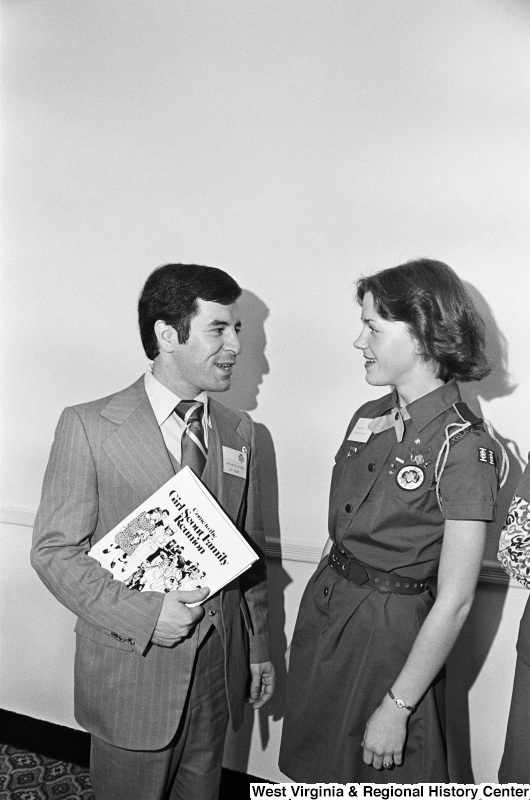 "Congressman Rahall stands with a Girl Scout and holds a book entitled ""Come to the Girl Scout Family Reunion."""