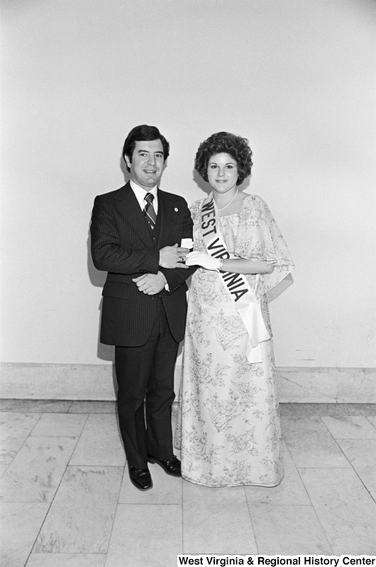 "Congressman Rahall stands next to a woman wearing a sash labeled ""WEST VIRGINIA."""
