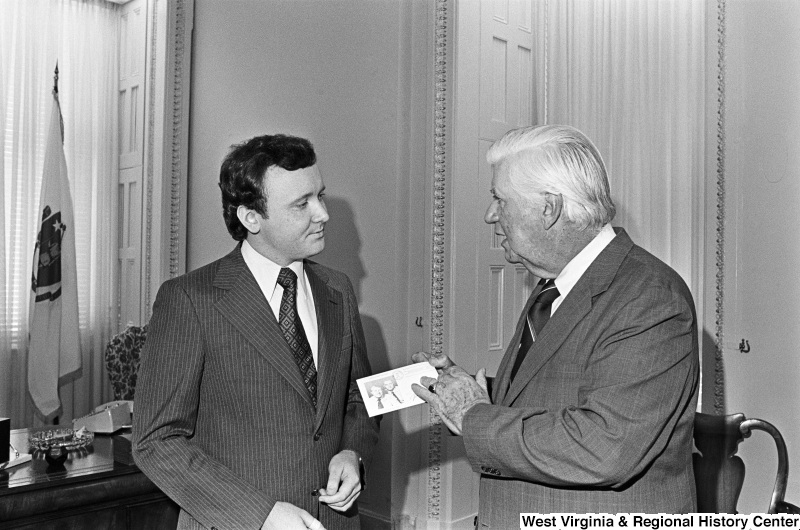"Tip O'Neill holds an ""Inauguration Day"" postcard bearing an image of President Carter and Vice President Mondale, while speaking to a man."