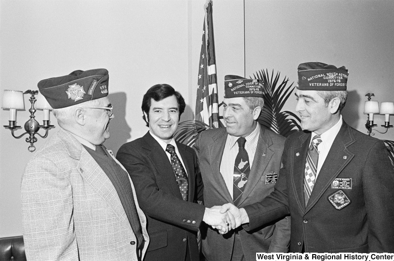 Congressman Rahall meets with three men, including Raymond H. Honaker and Ralph W. Honaker, who wear Veterans of Foreign Wars caps and insignias.