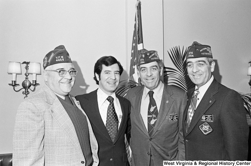 Congressman Rahall poses with Raymond H. Honaker, Ralph W. Honaker, and another man who wear Veterans of Foreign Wars caps and insignias.