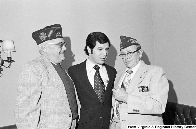 "Congressman Rahall stands with E.W. ""Pat"" Williams and Paul D. Dickerson, who wear Veterans of Foreign Wars caps and insignias."