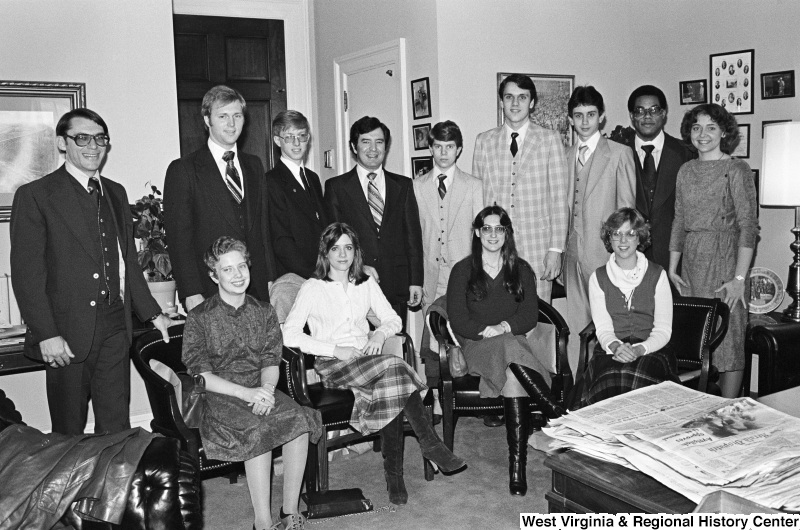 Congressman Rahall poses for a photograph with twelve men and women in an office.