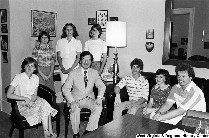Congressman Rahall poses for a photograph with seven people in an office.