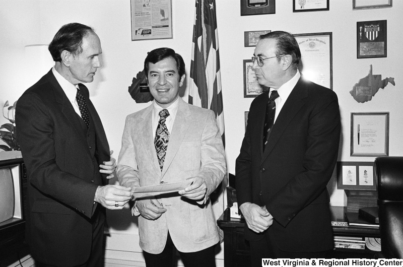 Congressman Rahall holds a paper and meets with two men in his office.
