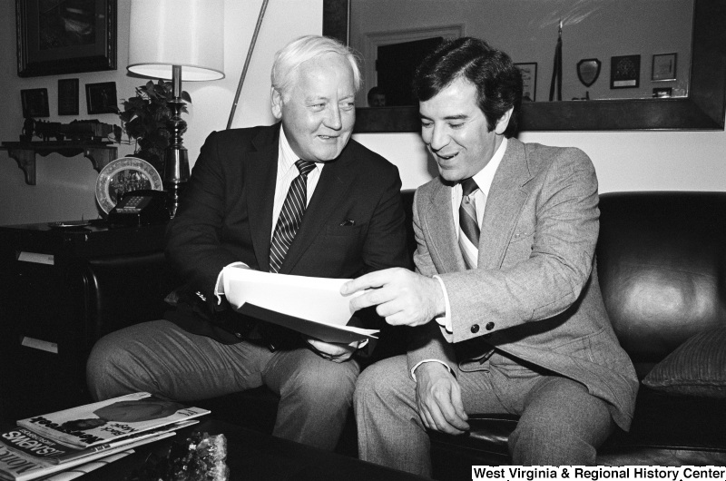 Congressman Rahall looks at documents with another man in an office.