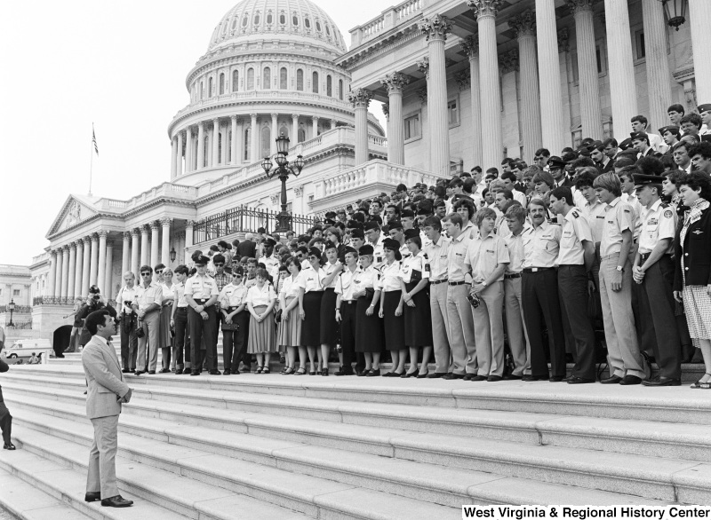 Congressman Rahall faces a large group of people wearing military uniforms on the steps of the Capitol Building.