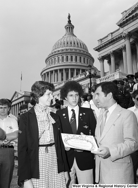 "Congressman Rahall stands on the steps of the Capitol Building holding a diploma presented by L'AERO CLUB DE FRANCE, while talking to a woman wearing a ""FRANCE"" insignia and another young man wearing badges and a tie bearing winged ACF insignias."