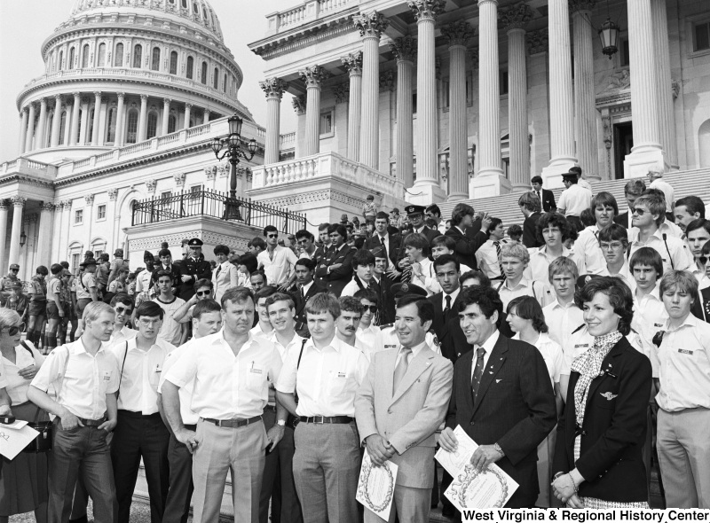 Congressman Rahall and Harrison Schmidt, among a group of people on the steps of the Capitol Building, hold diplomas presented by L'AERO CLUB DE FRANCE.