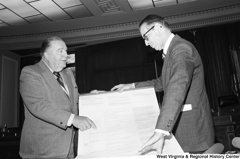 Jennings Randolph and another man examine a large print of a Washington family tree.