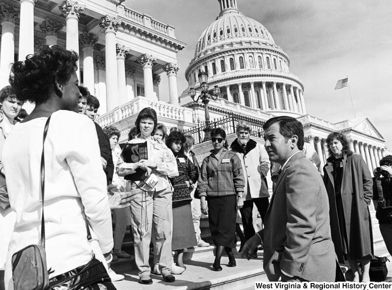 Photograph of Representative Nick Rahall on the steps of the Capitol Building with a group of unidentified people