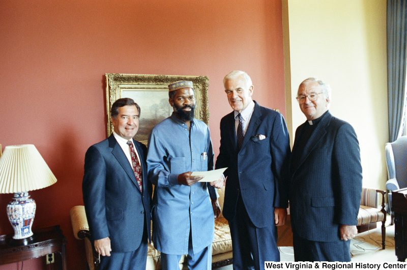 Photograph of Congressman Nick Rahall with Speaker of the House Tom Foley (WA), and House Chaplain David James Ford with an unidentified man