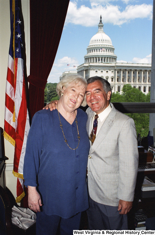 Photograph of Congressman Nick Rahall posing in his office with an unidentified woman