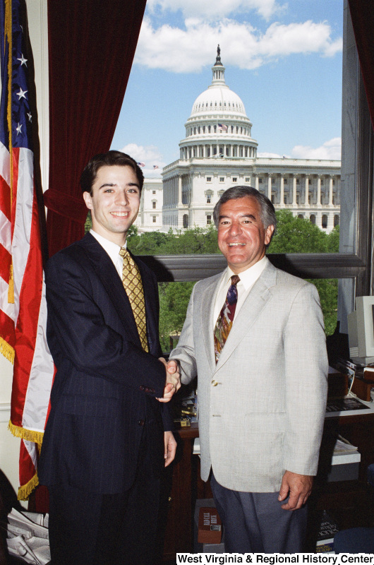 Photograph of an unidentified man posing with Congressman Nick Rahall in his office