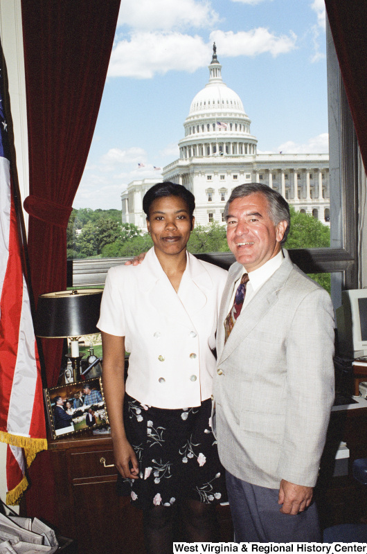Photograph of an unidentified female visitor posing with Congressman Nick Rahall