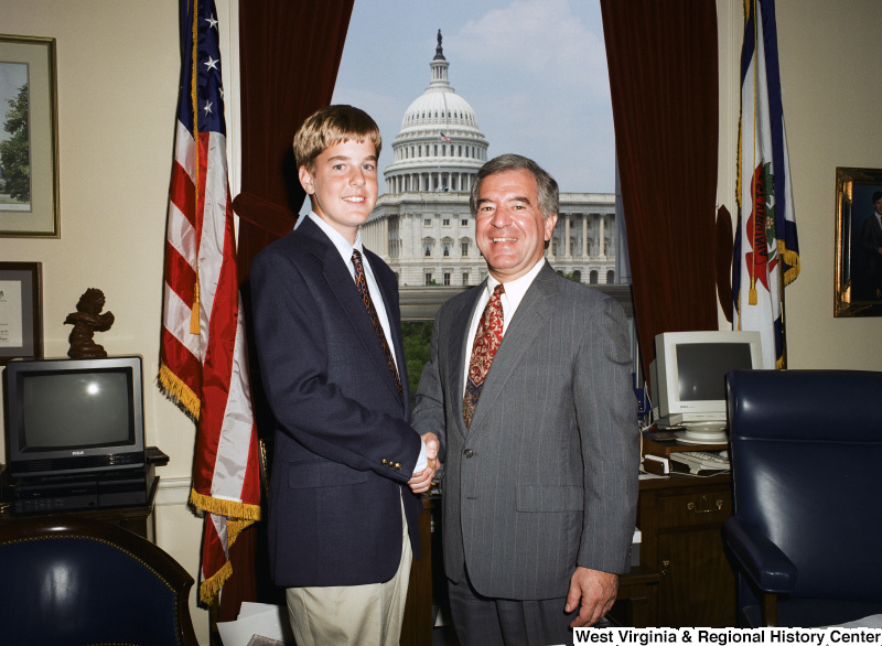 Photograph of an unidentified young man posing with Congressman Nick Rahall