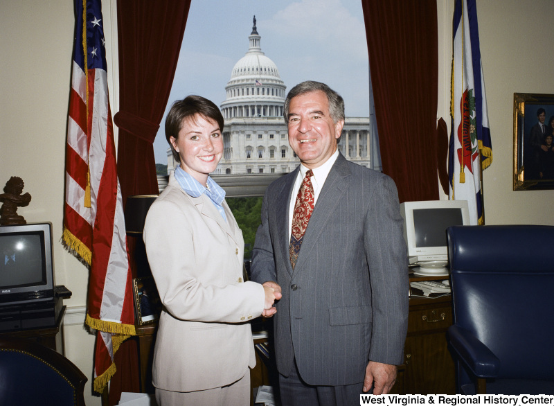 Photograph of an unidentified young woman posing with Congressman Nick Rahall in his office
