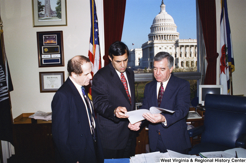 Photograph of Congressman Nick Rahall and two unidentified men looking over documents