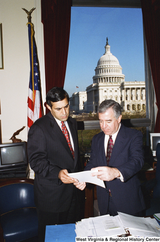 Photograph of an unidentified man and Congressman Nick J. Rahall looking over papers