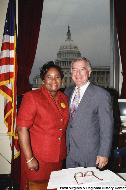 Photograph of an unidentified woman posing with Congressman Nick Rahall in his Washington office