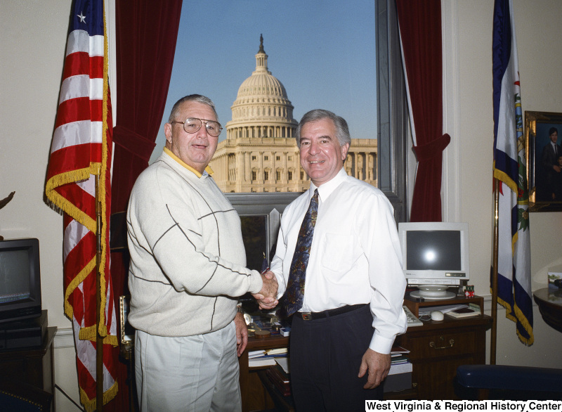 Photograph of Congressman Nick Rahall shaking hands with an unidentified visitor