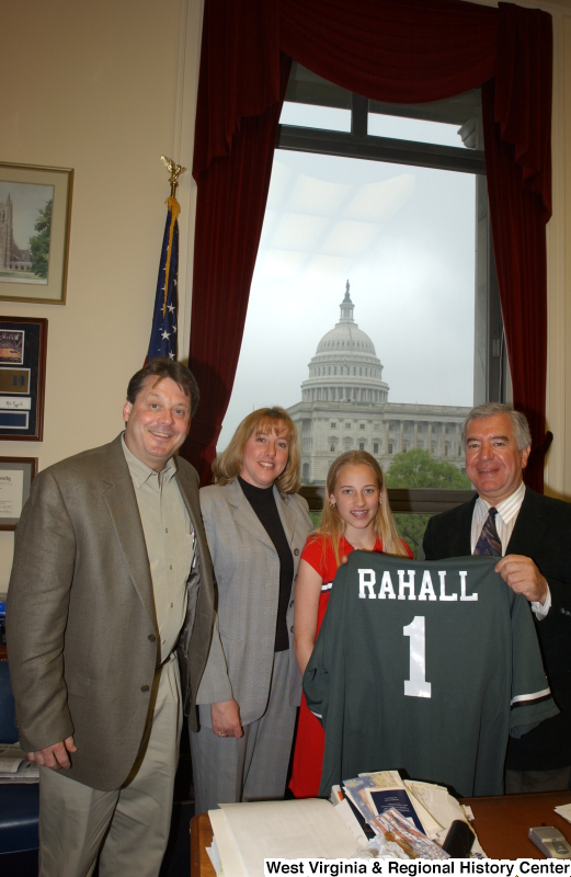 "Congressman Rahall holds a ""RAHALL"" sports jersey and stands with a man, woman, and girl in his Washington office."