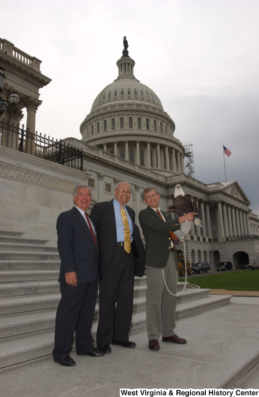 Congressman Rahall and John Dingell, Jr., stand with another man holding an eagle (facing camera) during a press conference in front of Capitol Building.