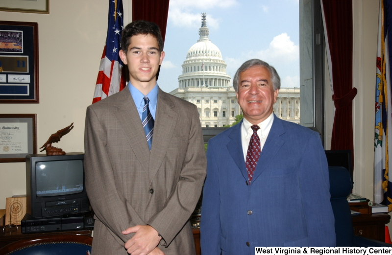 Congressman Rahall stands with a man wearing a taupe suit in his Washington office.