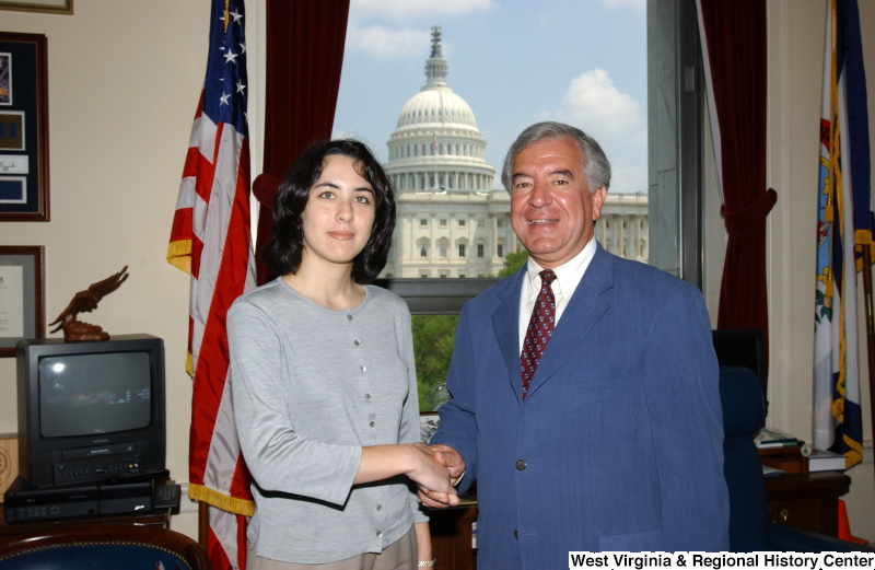 Congressman Rahall stands with a woman wearing a grey shirt in his Washington office.