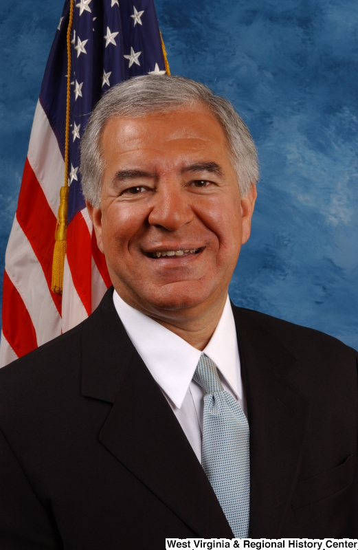 Congressman Rahall poses in front of the U.S. flag and a blue background  (portrait).
