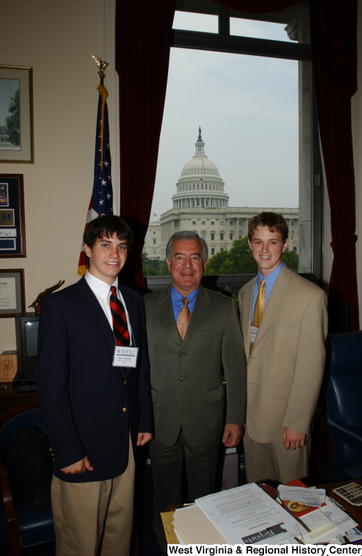 Congressman Rahall stands with two men wearing NYLC badges in his Washington office.