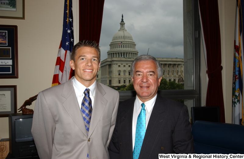 Congressman Rahall stands with a man wearing a grey suit in his Washington office.