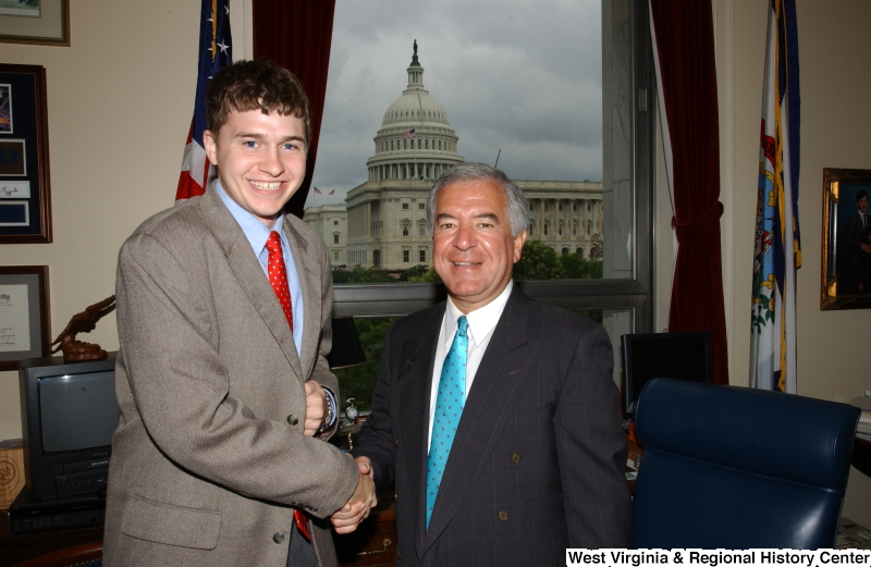 Congressman Rahall stands with a man wearing a taupe suit and red tie in his Washington office.