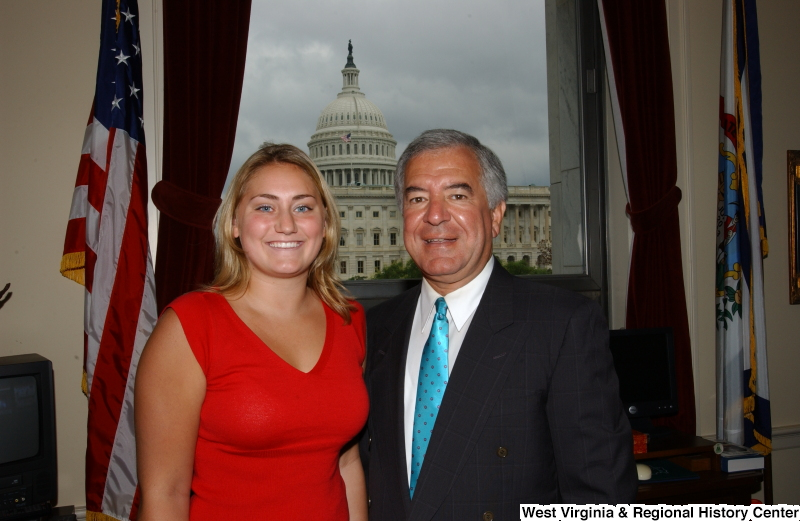 Congressman Rahall stands with a woman wearing a red shirt in his Washington office.