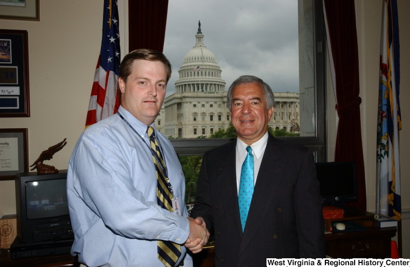 Congressman Rahall stands in his Washington office with a man wearing a blue shirt and striped tie.
