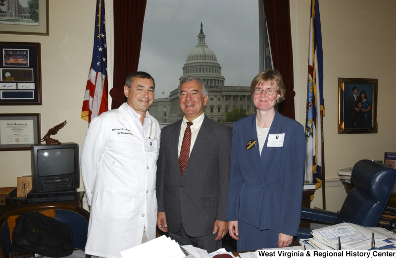 Congressman Rahall stands in his Washington office with Michael Krasnow, Doctor of Ophtalmology, and an unidentified woman.