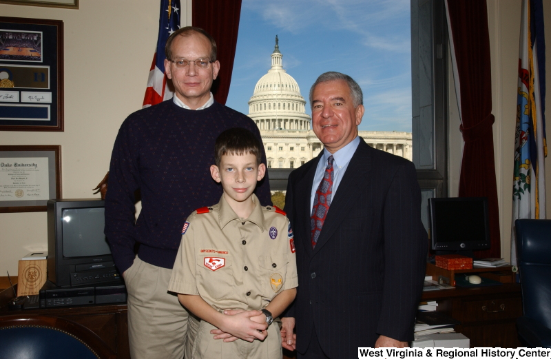 Congressman Rahall stands in his Washington office with a man and a Boy Scout.