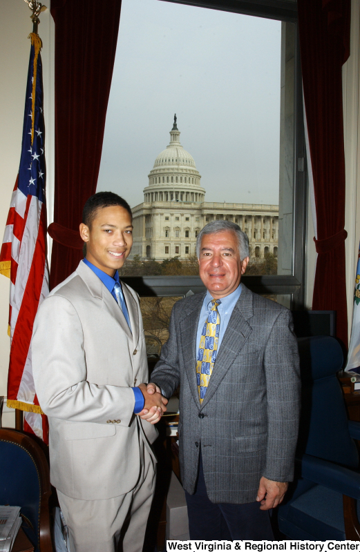 Congressman Rahall stands in his Washington office with a man wearing a light grey suit.