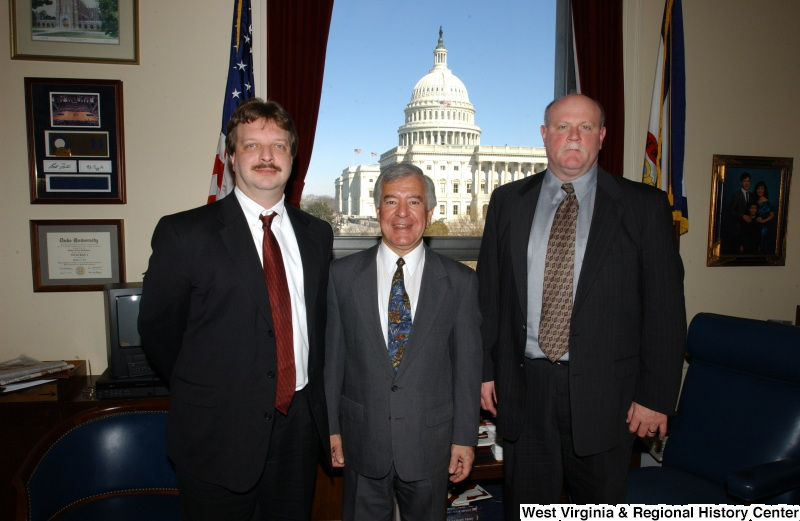Congressman Rahall stands in his Washington office with two men.