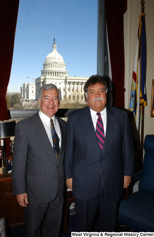 Congressman Rahall stands in his Washington office with a man wearing a dark suit and striped tie.