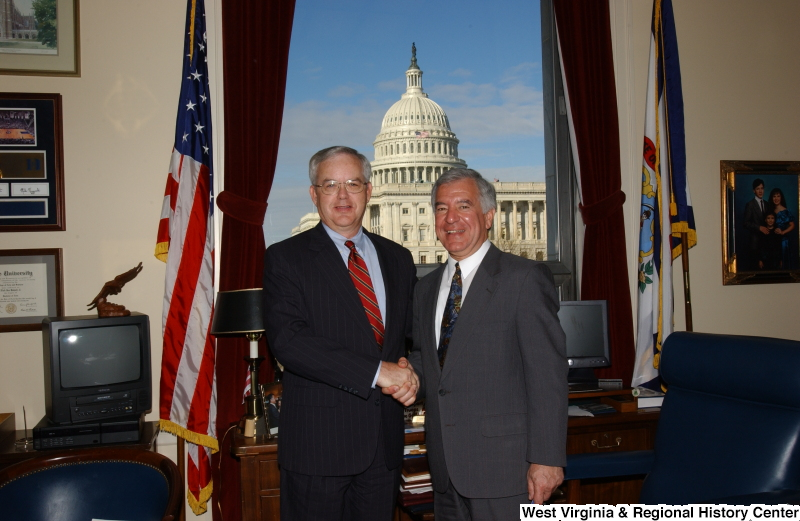 Congressman Rahall stands in his Washington office with a man wearing a pinstripe suit and red striped tie.