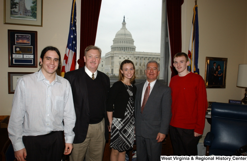 Congressman Rahall stands in his Washington office with three men and one woman.