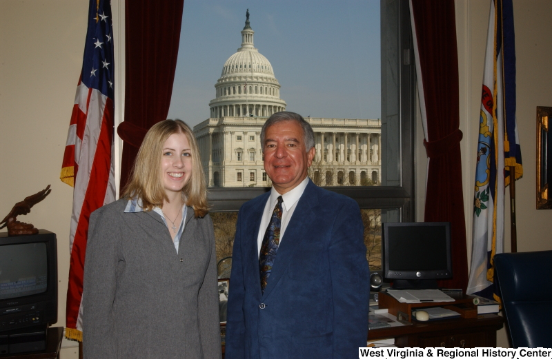 Congressman Rahall stands in his Washington office with a woman wearing a grey jacket.