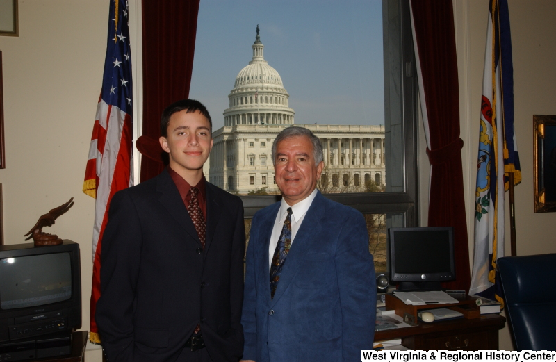 Congressman Rahall stands in his Washington office with a man wearing a dark suit and burgundy shirt.