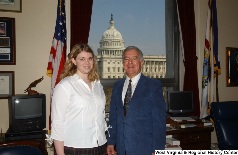 Congressman Rahall stands in his Washington office with a woman wearing a white blouse.