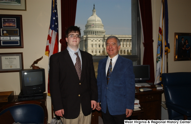 Congressman Rahall stands in his Washington office with a man wearing a dark blazer and khaki pants.