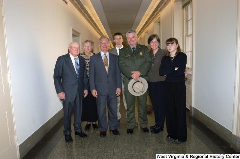Photograph of Congressman Rahall standing in a hallway with a man from the Park Service and five other people