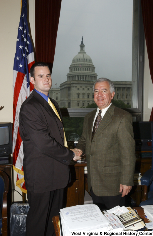 Congressman Rahall stands in his Washington office with a man wearing a black suit and yellow tie.