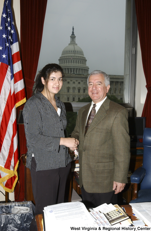Congressman Rahall stands in his Washington office with a woman wearing a black and grey striped shirt.