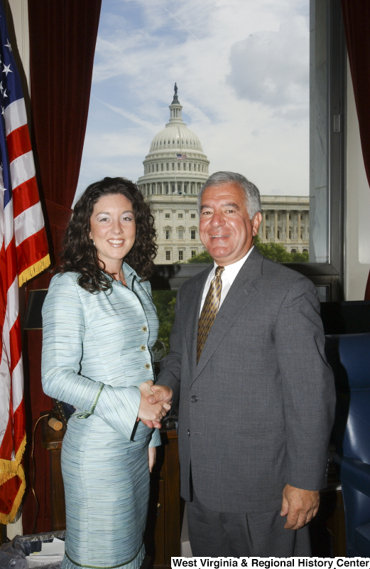 Congressman Rahall stands in his Washington office with a woman wearing an aqua dress.